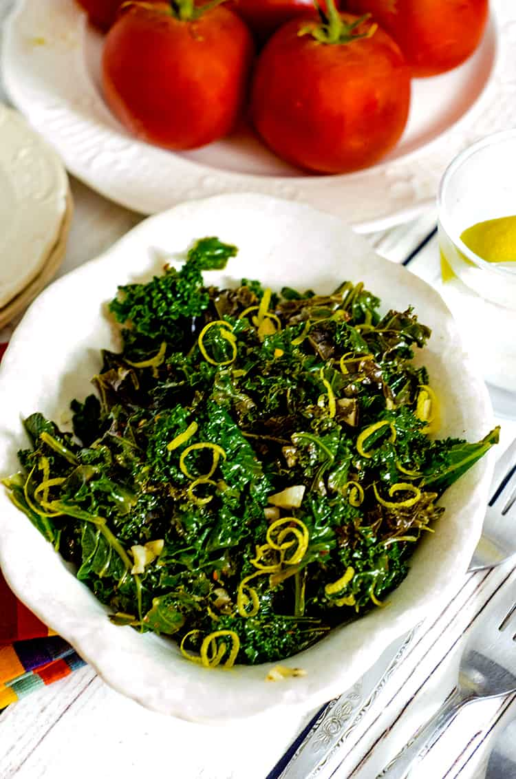 Bowl of steamed kale with lemon zest garnish.