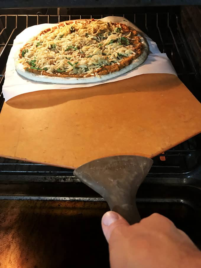 Use a pizza peel to transfer pizza to hot stone.