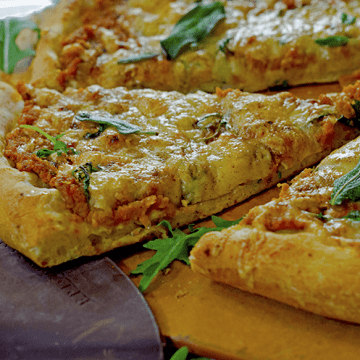 A slice of pumpkin pizza with fresh herbs atop board and peel
