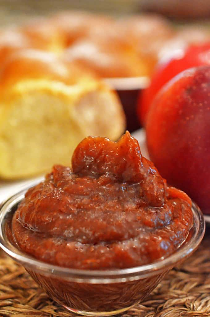serving dish of apple butter with a dinner roll in the background.