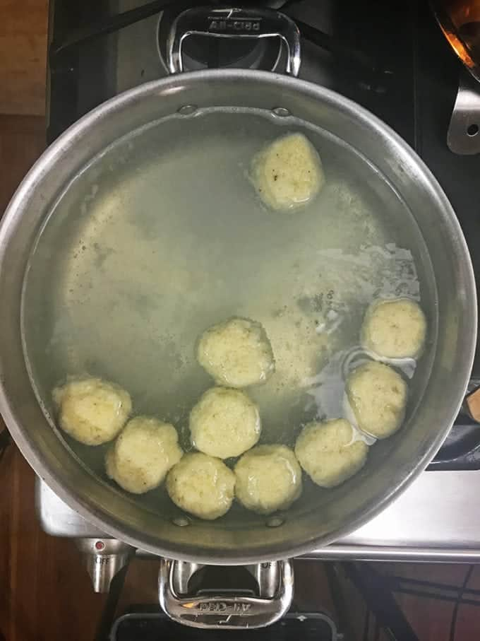 Potato dumplings rise to the top of the hot water.