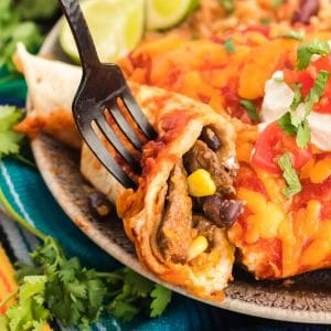 Table fork cutting into a beef enchilada