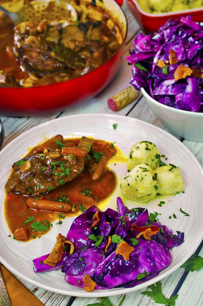 Dinner plate with braised pork and carrots, potatoe dumplings, and purple cabbage,