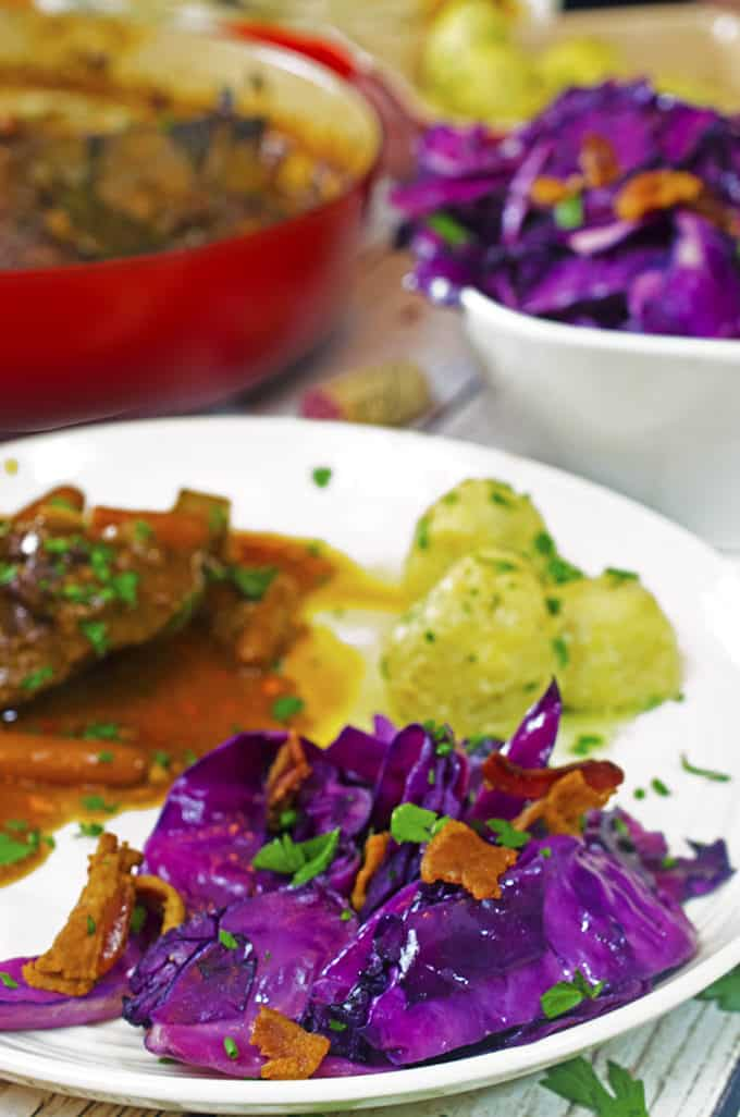 White dinner plate with braised pork, potato dumplings, and purple fried cabbage and bacon.