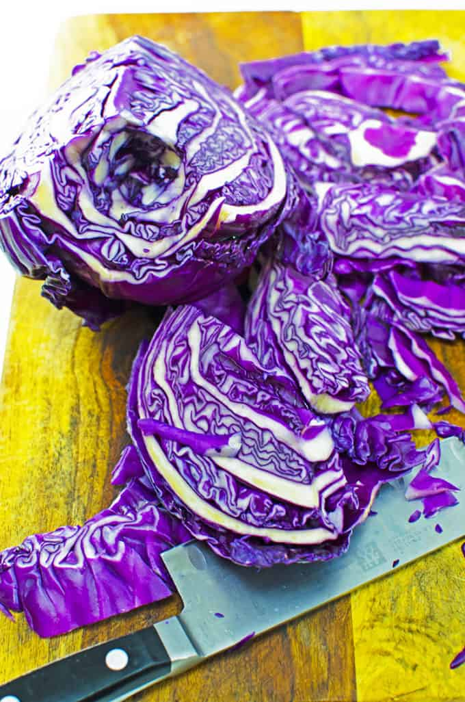 Slicesd purple cabbage on a cutting board with a chef's knife.
