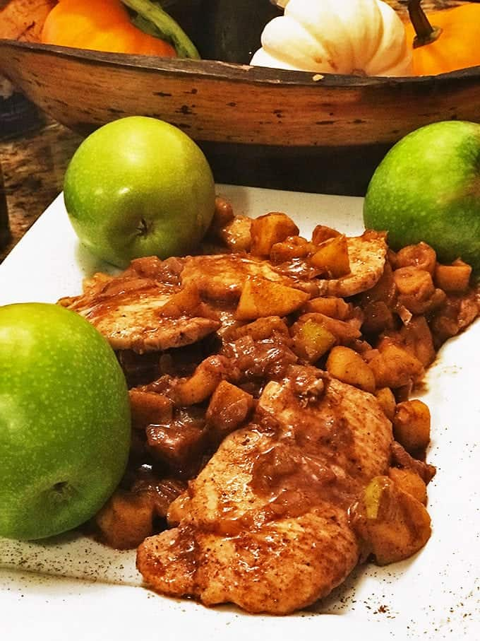 Plated pork chop in cooked vegetables with 3 green apples