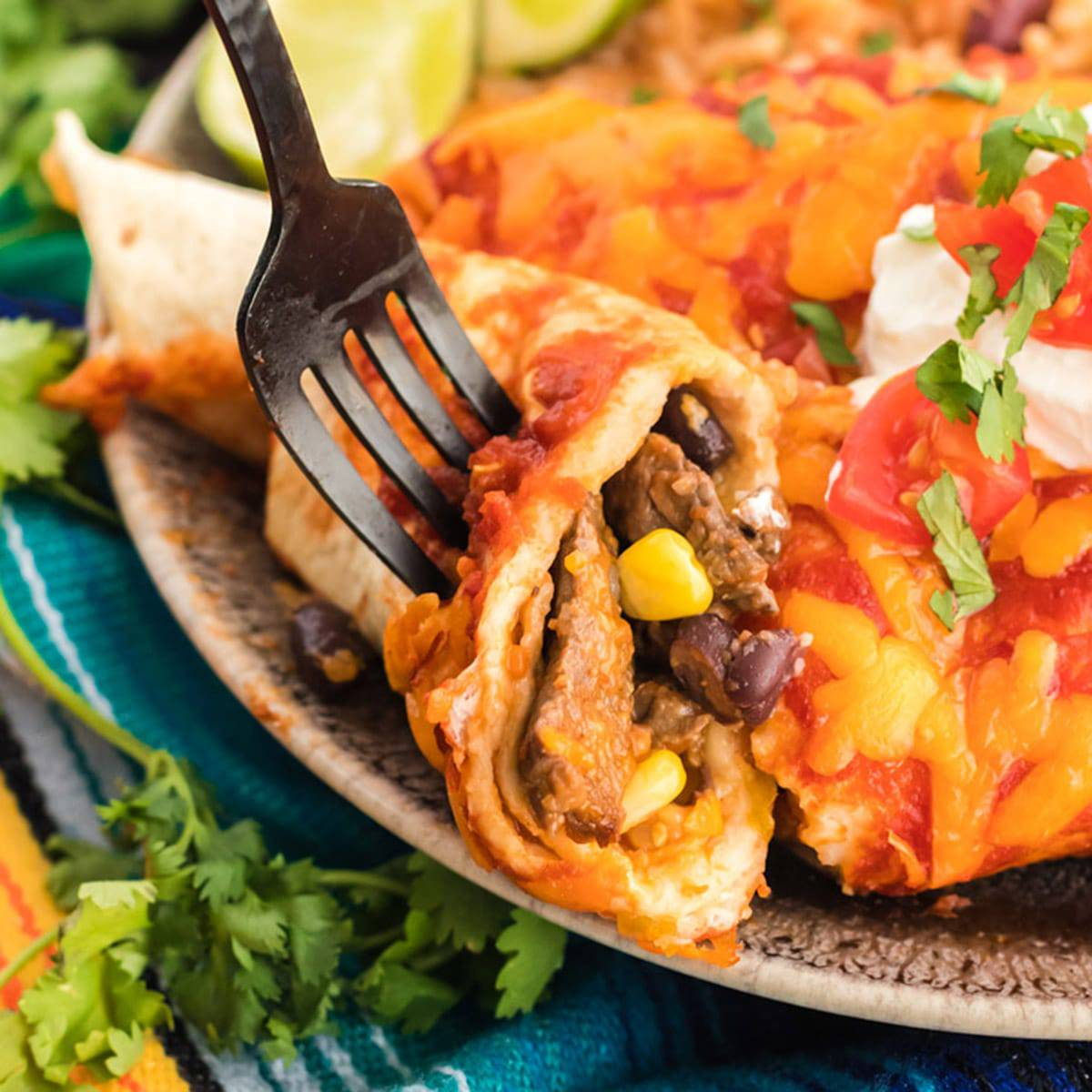 Using a fork to eat an enchilada made with leftover steak.