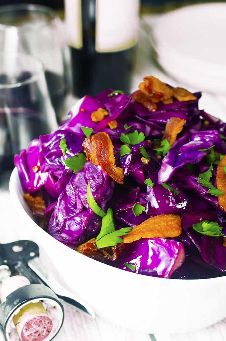 White bowl full of purple fried cabbage with pieces of bacon and Italian parsley.