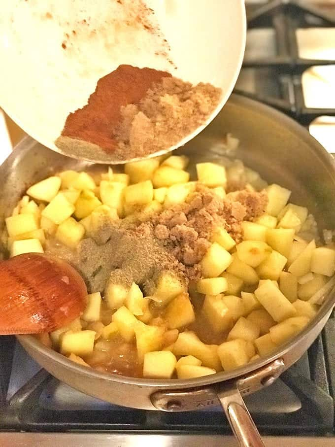 Spices being added to pan of cooking apples with wood spoon