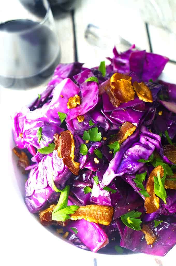 Bowl of purple fried cabbage with bacon and parsely garnsih and a glass of wine.
