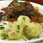 Serving of pork roast with three potato dumplings garnished with parsley.