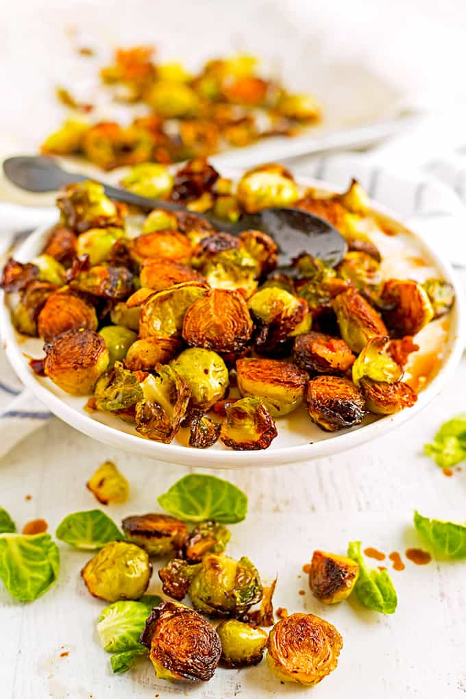 Roasgted brussels sprouts with balsamic and garlic on a white platter.