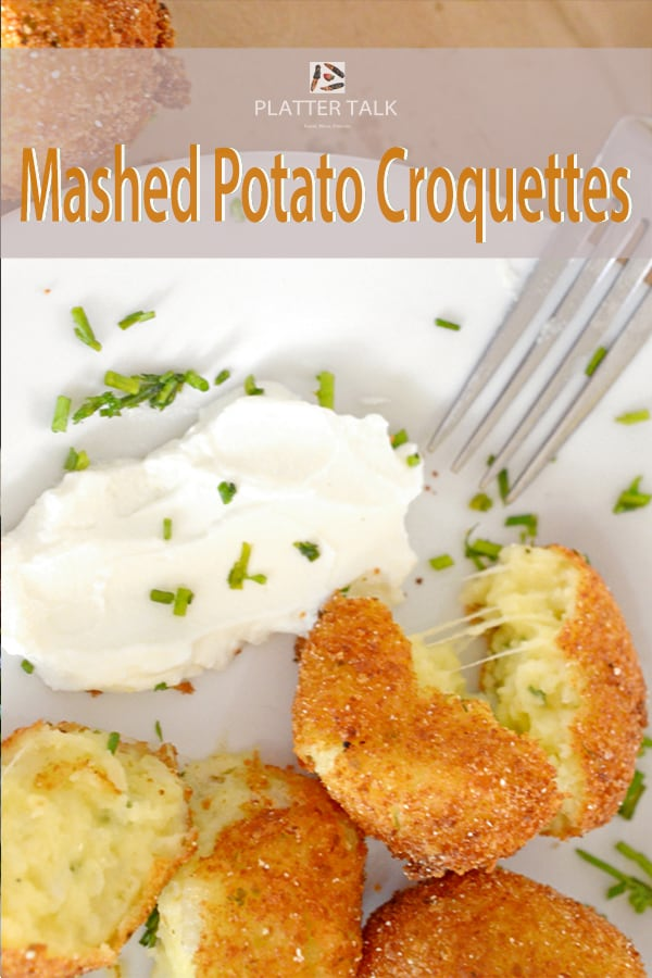 Plate of mashed potato croquettes with fork and sour cream.