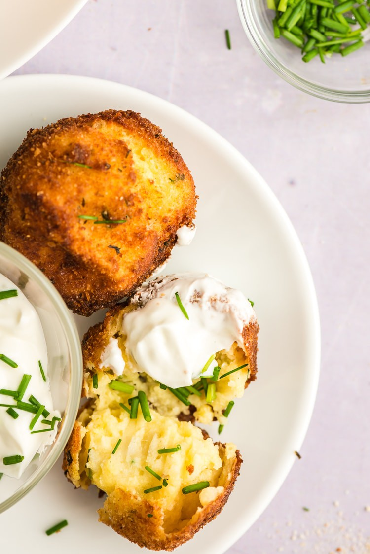 Plate of potato croquettes with sour cream and chives.
