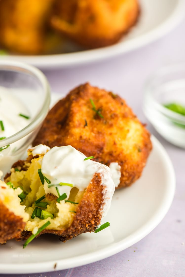 Plate of mashed potato croquettes with sour cream.