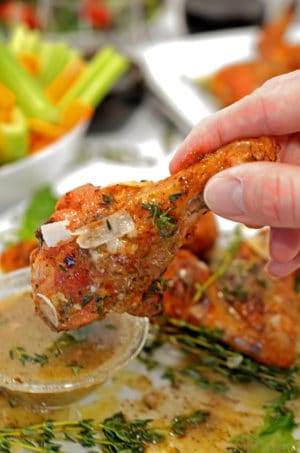 dipping Italian chicken wings in sauce.