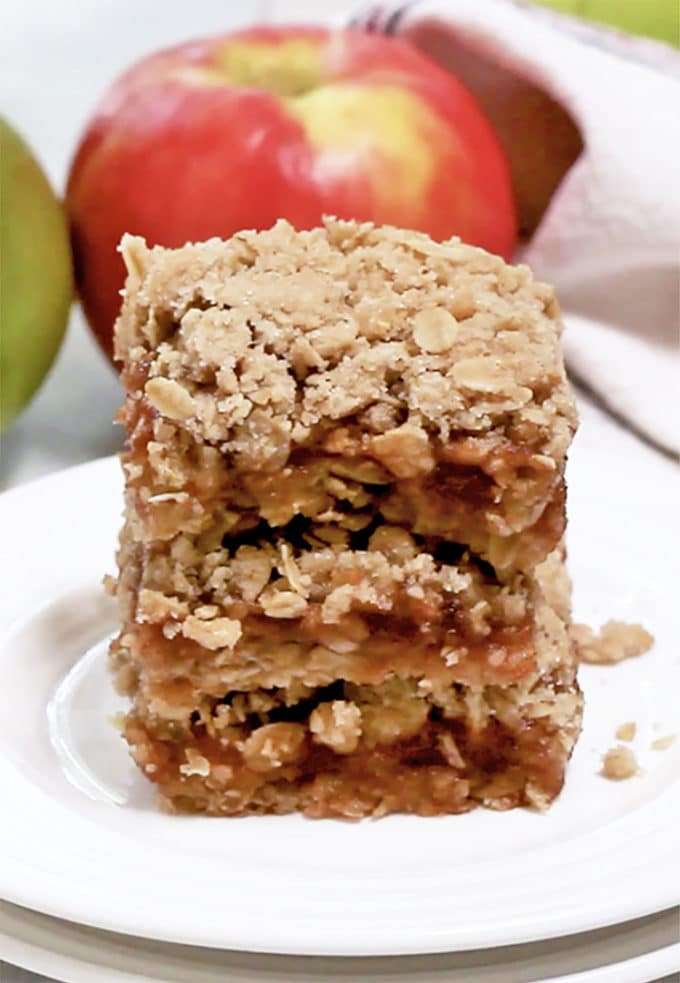3 oatmeal bars, stacked on white plate with apple in background.