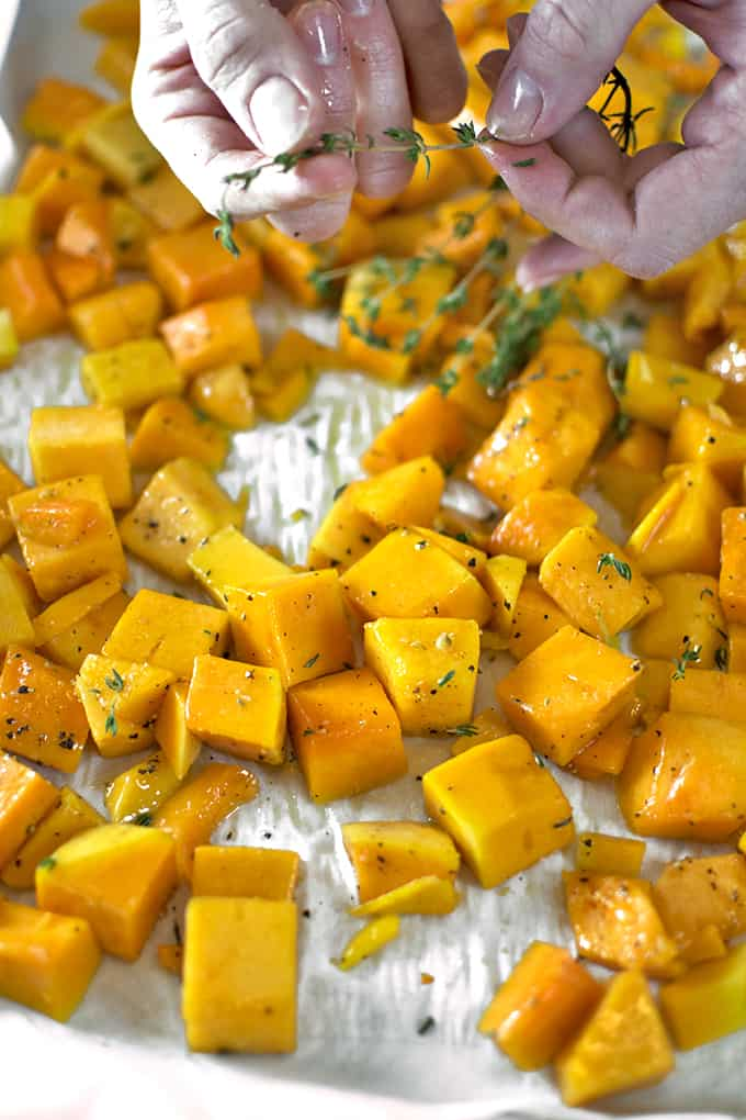 Adding fresh thyme to butternut squash soup recipe.