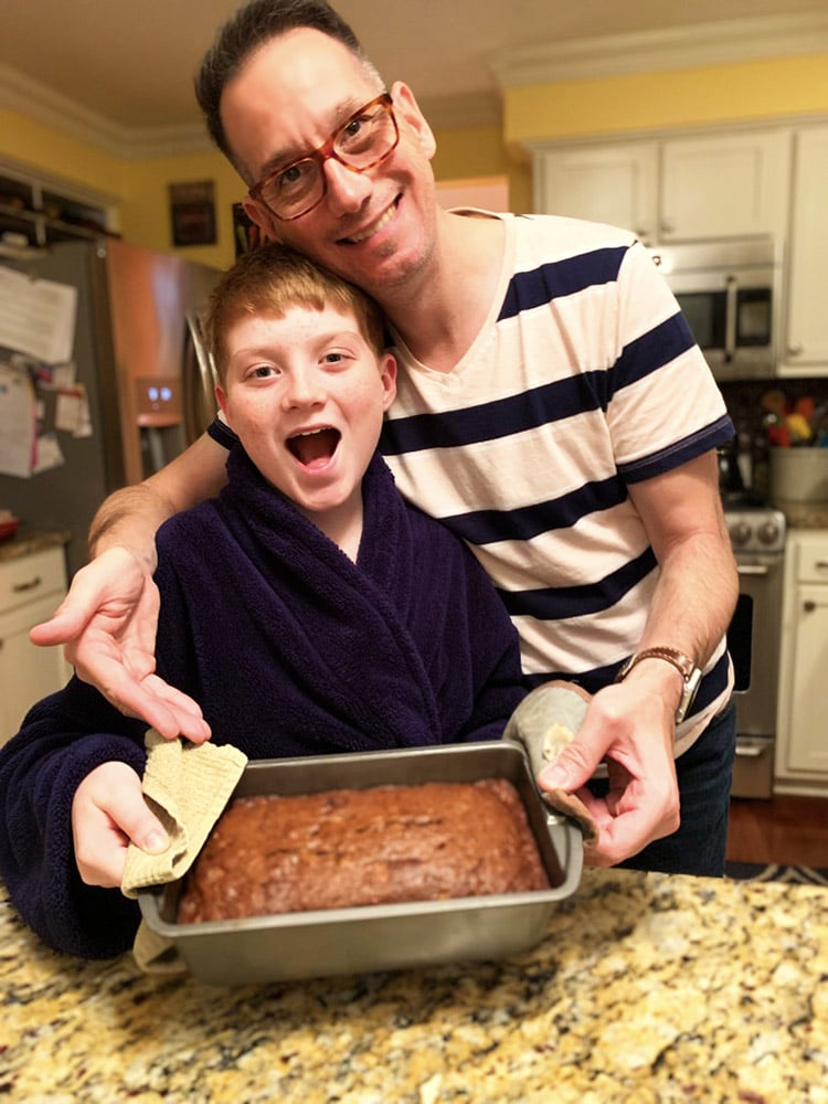 teenage boy holding a loaf of homemade banana bread with his father.
