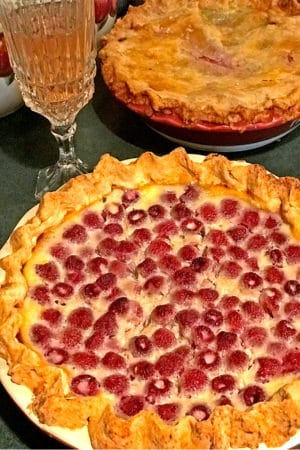 Two homemade pies with galss of white wine.
