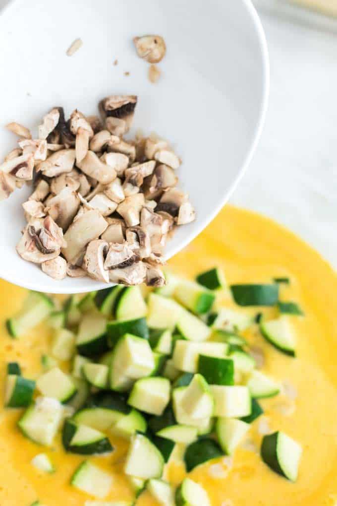 Adding mushrooms to a veggie quiche.