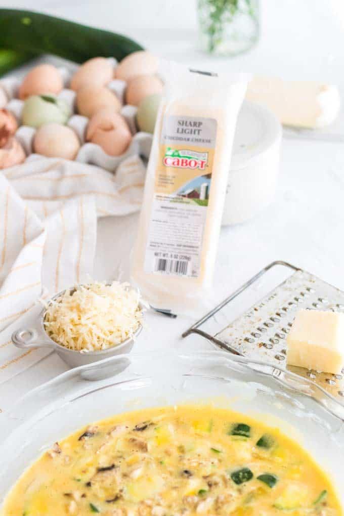 Adding cheddar cheese to veggie quiche.
