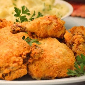 Plate of oven-fried chicken with parsley garnishes.