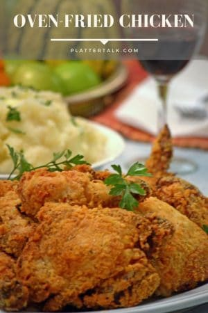 Serving plate of oven-fried chicken with mashed potatoes and a glass of red wine.