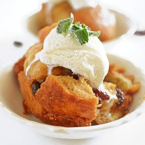 A bowl of bread pudding with vanilla ice cream on top
