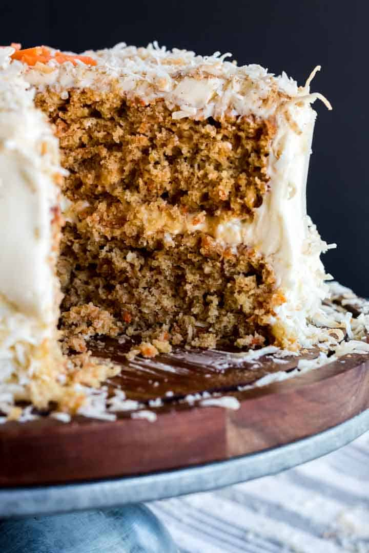 coconut carrot cake sliced open, showing rich layers of crumbs and frosting.