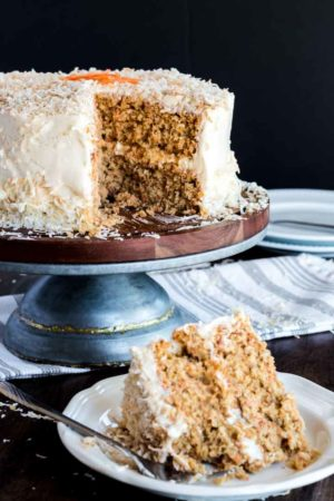 Slice of homemade carrot cake and cut cake in the background.