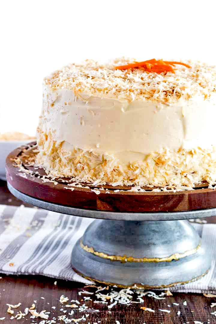 homemade carrot cake on a pedistal with toasted coconut cream cheese frosting.