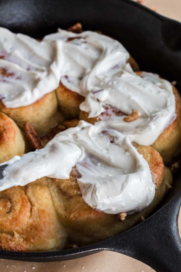 spreading sugar-free frosing on fresh keto cinnamon rolls.