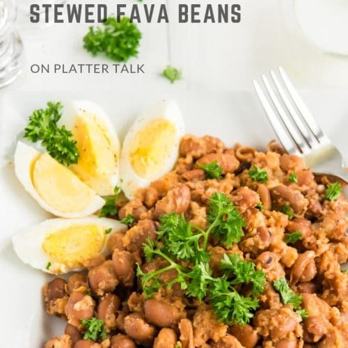 Plate of stewed fava beans with hard-boiled egg and parsley.