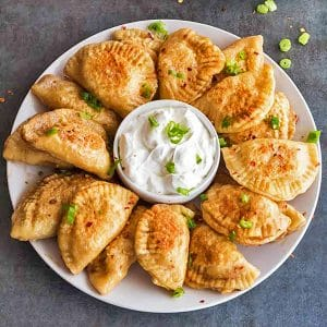Round plate of pierogi with sour cream in the center.