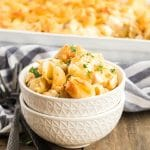 Bowl of baked pasta shells with chicken casserole in the background.