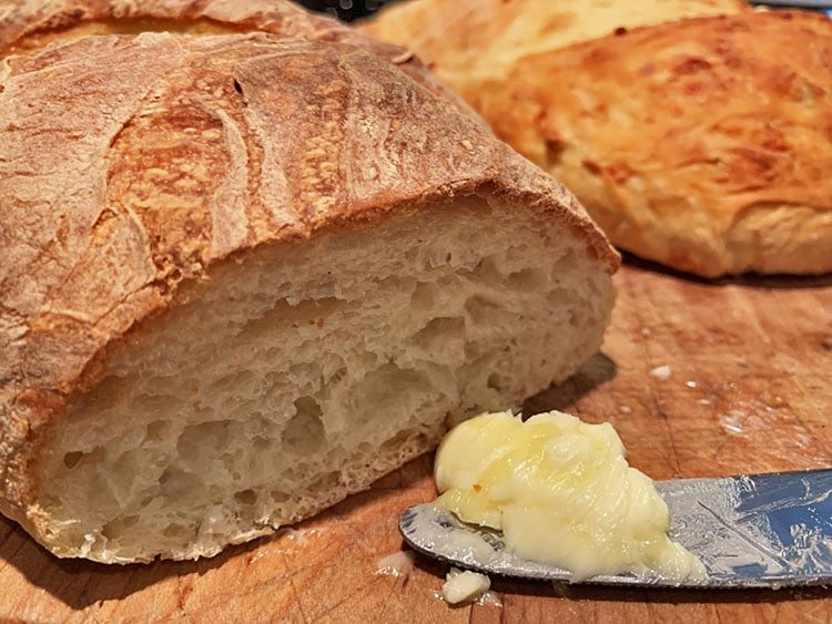 loaf of homemade artisan breads with a dollop of butter on a knife.