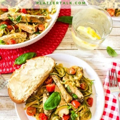 Plate of zoodles recipe with boneless skinless chicken breasts and slice of bread.