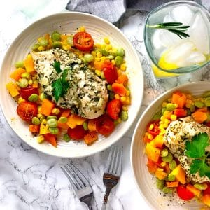 Two bowls of summer succotash topped with chicken breast and a glass of ice water.