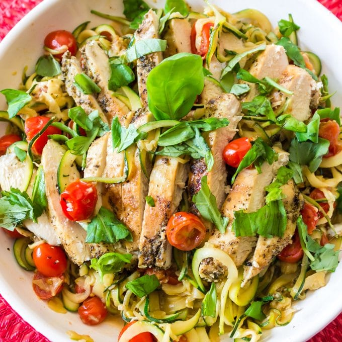 Bowl of chicken covered with shredded basil.