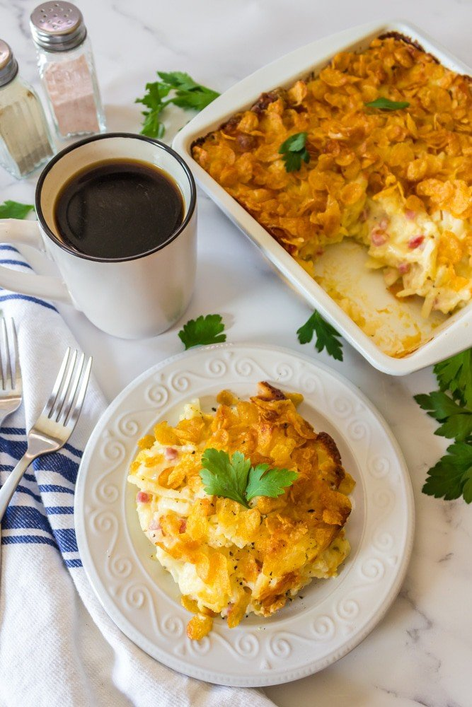 Serving of cheesy hashbrown casserole with cup of coffee.