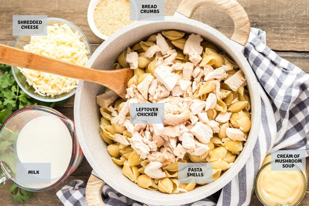 Bowl containing pasta shells and chunks of chicken, surrounded by ingredients to make a chicken casserole.