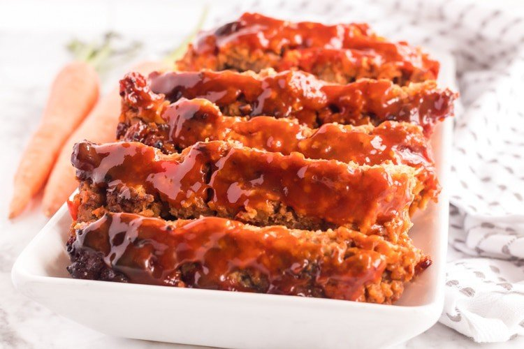 Plate of meatloaf with whole carrots on the side.