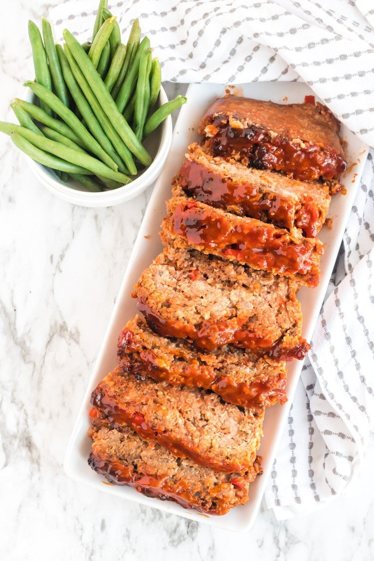Whole meatloaf on a serving plate, cut into pieces with green beans on the side.