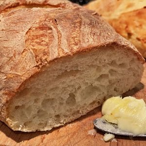 Cut loaf of crusty bread with butter and butter knife.