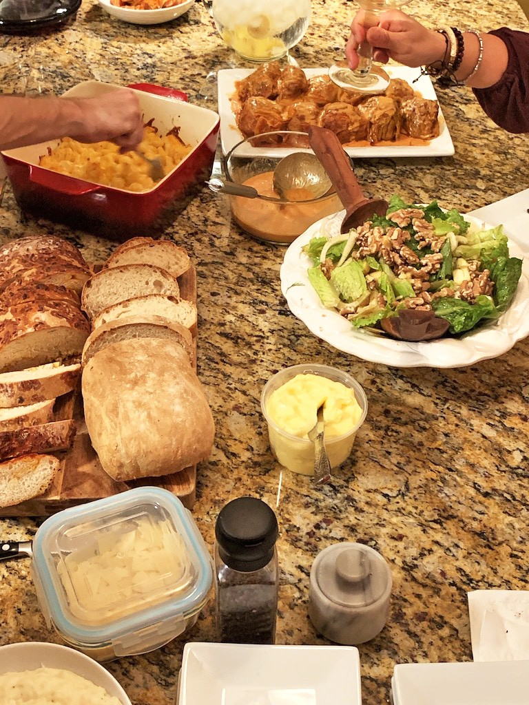 Dinner party food with crusty bread, golumpki, green salad, mac and cheese, and butter.