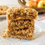 stack of three oatmeal dessert bars with appeles in the background,.