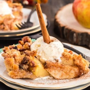 Dutch apple pie on a plate with ice cream and a cinnaomn stick.