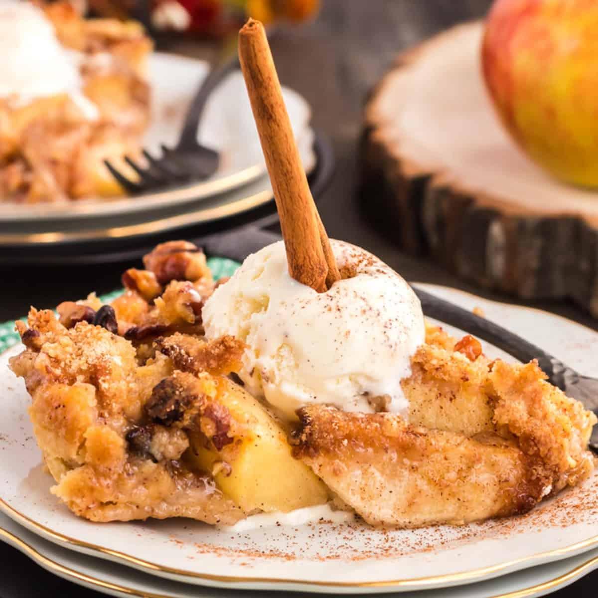 Dutch apple pie on a plate with ice cream and a cinnaomn stick.