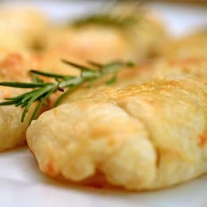 Some food on a plate with rosemary spirg